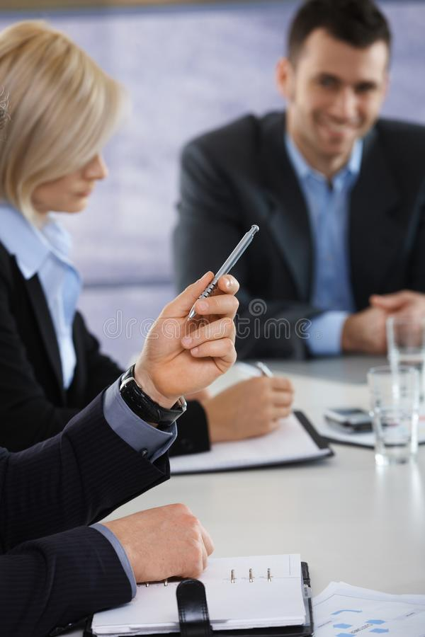 Hands on business meeting at office. Closeup of hands on business meeting at office, businessman pointing with pen royalty free stock images