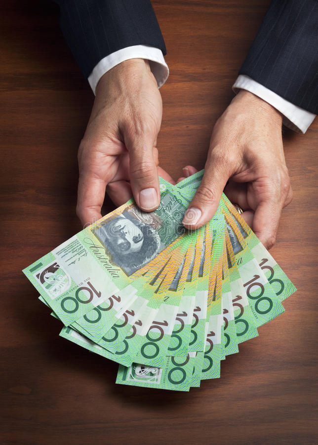 Australia Australian Hands Business Money Dollars Superannuation. A businessman holding a large quantity of Australian money in his hands on a wood desk surface royalty free stock images