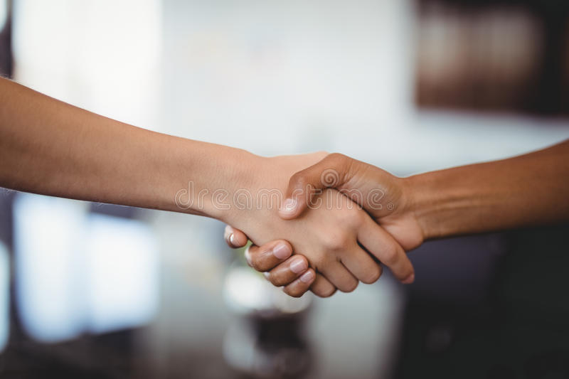 Hands of business people shaking hands in office royalty free stock image