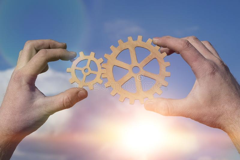 Hands businessman holding gears on the background of the sky in the sun, connecting the puzzle pieces. Creation. mechanism. Business idea concept, teamwork royalty free stock images