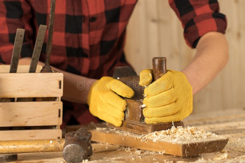 Hands of a carpenter planed wood, workplace. Carpenter sucks a wooden board royalty free stock photography