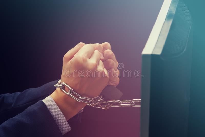 Hands of caucasian businessman addicted to internet and locked with iron chain wrists, smartphone internet addiction and slave to royalty free stock images