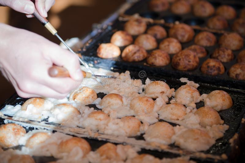 Hands of chef cooking Takoyaki ball dumplings or Octopus balls. Takoyaki balls are made with octopus, wheat flour-based batter and stock image