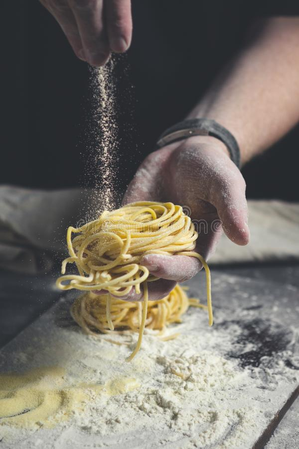 The hands of the chef sprinkled with flour fresh pasta royalty free stock image