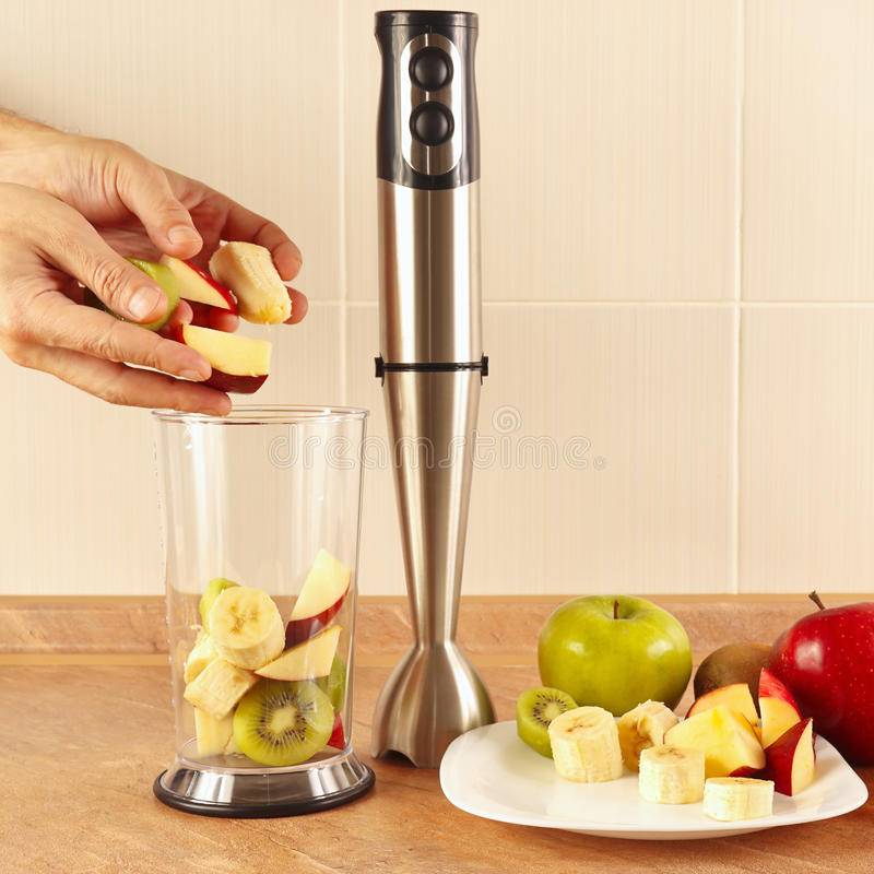 Hands chefs put the fruit in the blender to prepare the smoothie on table royalty free stock image