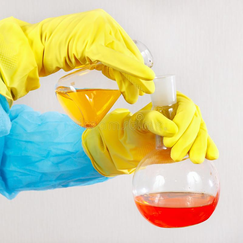Hands of chemist in rubber gloves doing chemical research in laboratory stock images