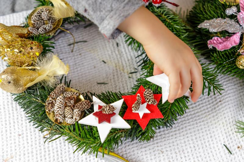 Hands of a child decorate Christmas Advent wreath from fir twigs stock photo