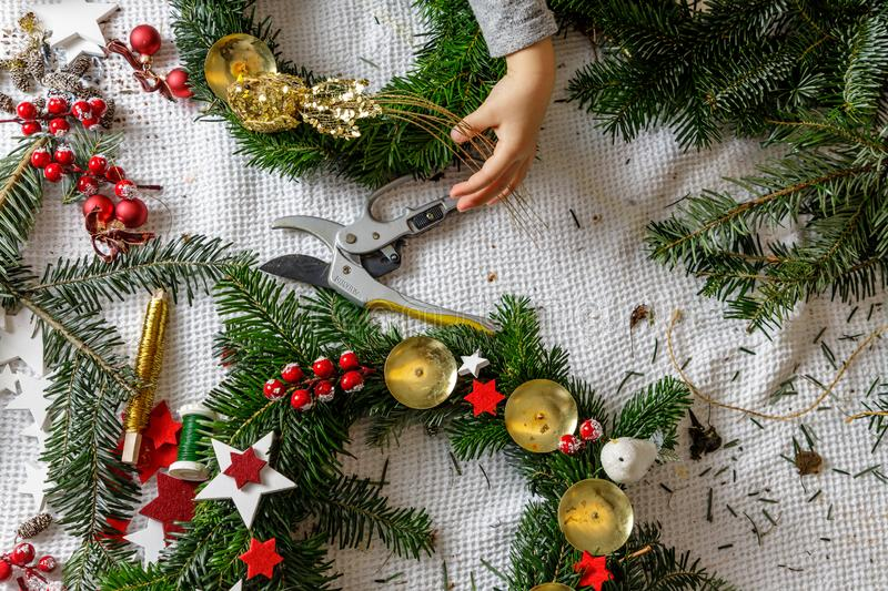 Hands of a child decorate Christmas Advent wreath from fir twigs royalty free stock photos