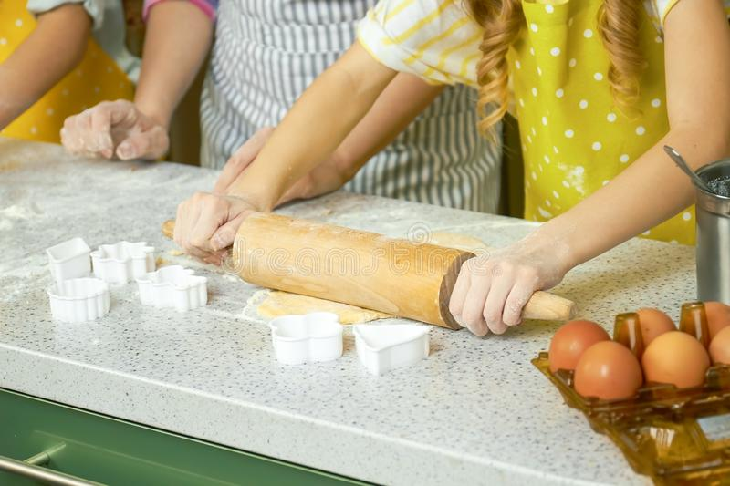 Hands of child rolling dough. royalty free stock images