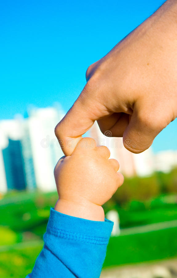 Hands of child son and father stock image