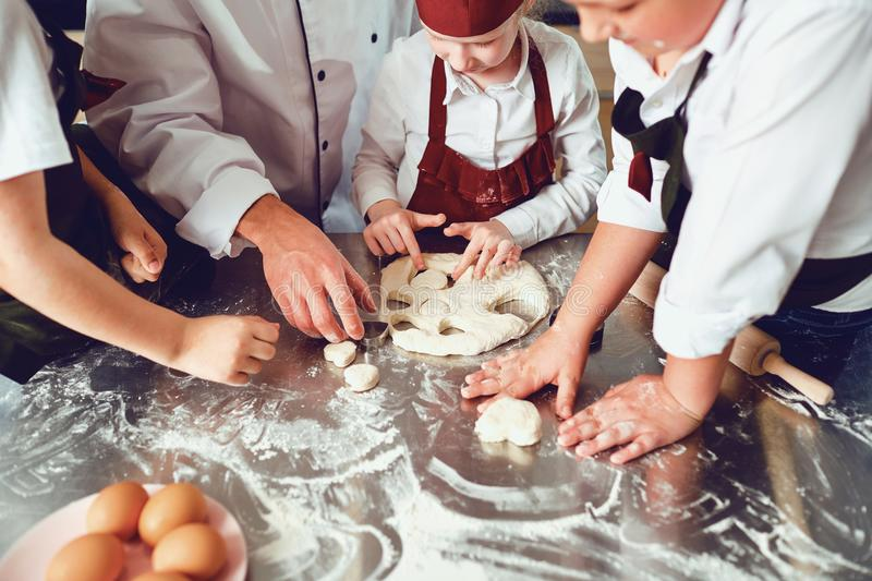 Hands of children close-up cook a cookie on the table. royalty free stock photography