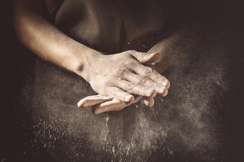 Hands clapping with flour. Unrecognizable cook clapping hands with flour while making dough stock photo