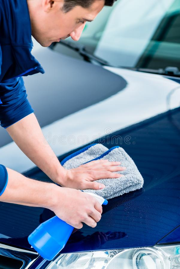 Hands cleaning car with spray cleaner and microfiber towel. Close-up of male hands cleaning car with spray cleaner and microfiber towel outdoors at car wash stock photo