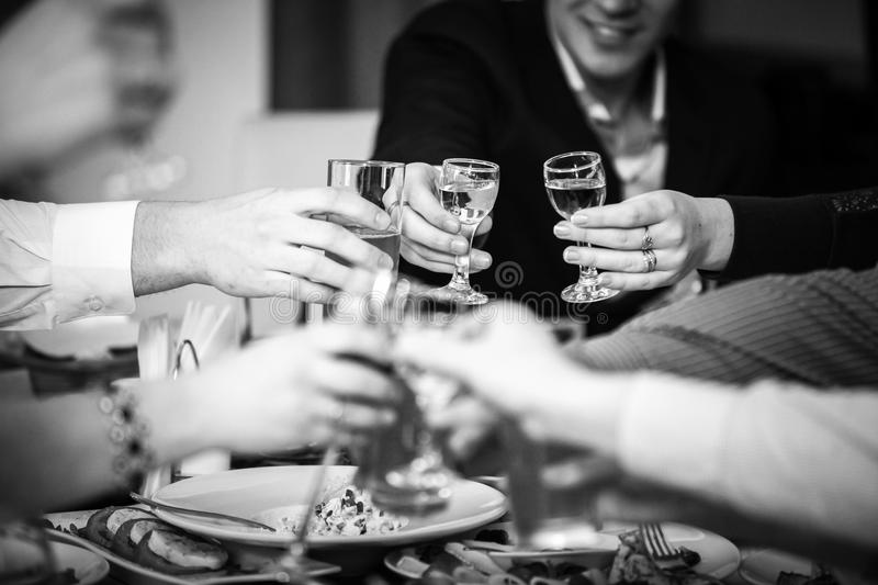 Hands clinking glasses at restaurant stock images