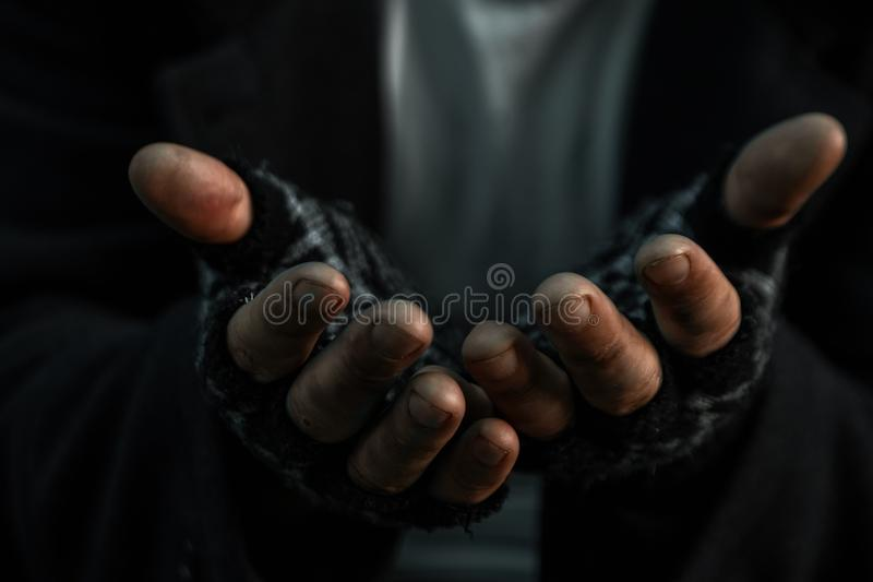 Hands close up poor old man or beggar begging you for help sitting at dirty slum. Concept for poverty or hunger people,human stock image