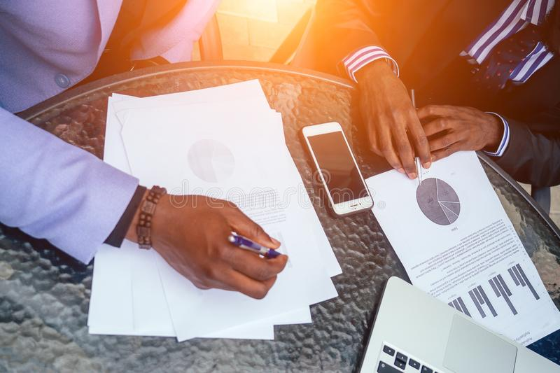 Hands closeup of group black afro american men in stylish business suit, expensive wristwatch sit at the table with. Laptop, securities and contracts. concept stock images