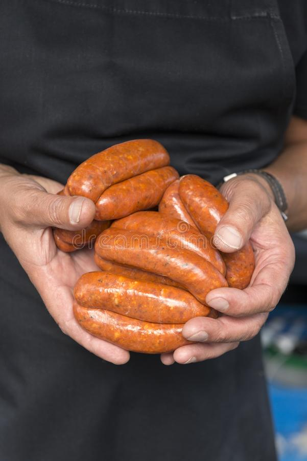 Hands Clutching Raw Sausage Links stock image