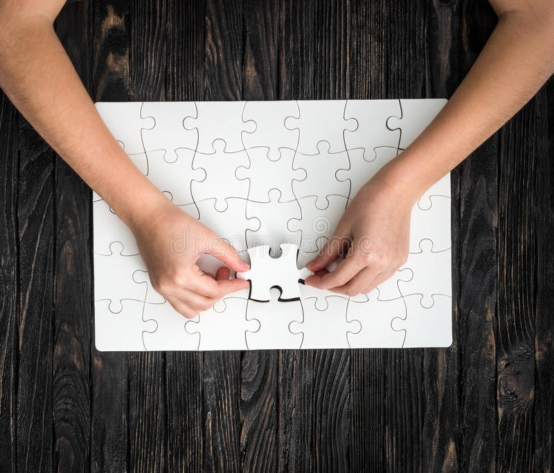 Hands completing wthite puzzle with the last piece stock images
