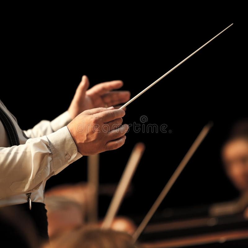 The hands of the conductor on the background of the orchestra. In dark colors stock photos
