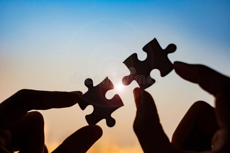 hands connecting couple puzzle piece against sunrise effec royalty free stock photos
