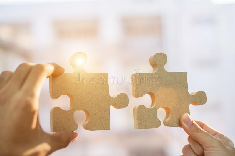 Hands connecting couple puzzle piece against sunrise effect, businesswoman and business man holding wood jigsaw with sunset. Background. Business solutions royalty free stock photos