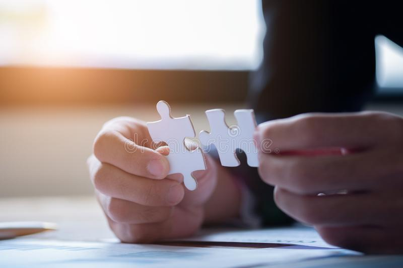 Hands connecting jigsaw puzzle. Business solutions, success and strategy concept. Close up photo with selective focus stock images