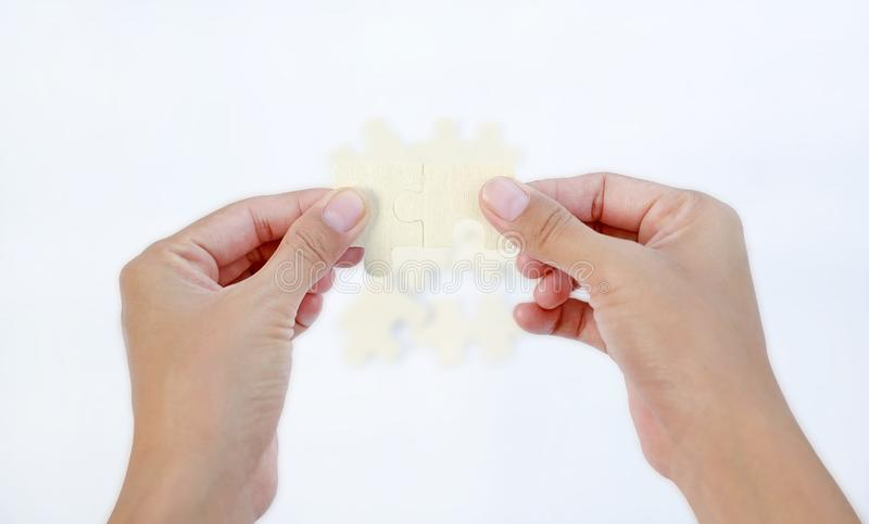 Hands connecting jigsaw puzzle isolated on white background stock photo