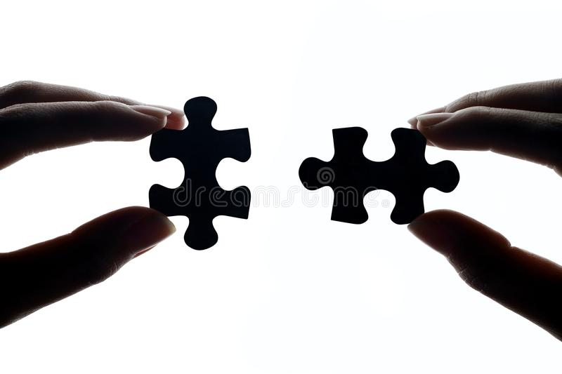 Hands Connecting Jigsaw Puzzle Pieces stock photo