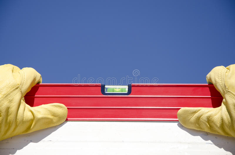 Hands with gloves on spirit level outdoor construction royalty free stock images