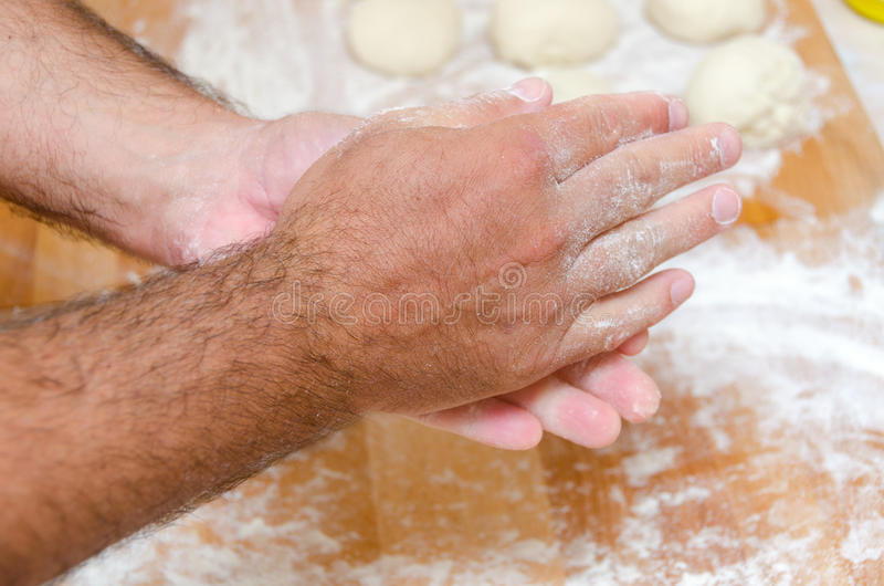 Hands of the cook. While preparing the pizza dough stock image