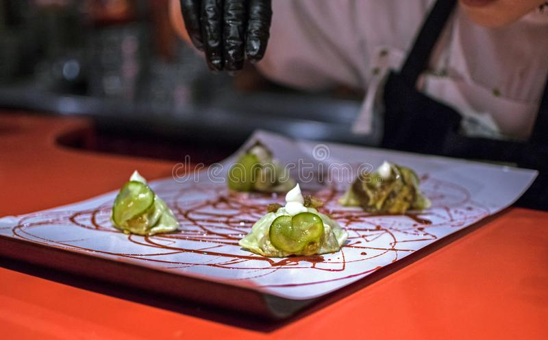 Hands cooking gourmet dish. Pekinese dumplings of ear& x27;s pig served with hoisin sauce royalty free stock image