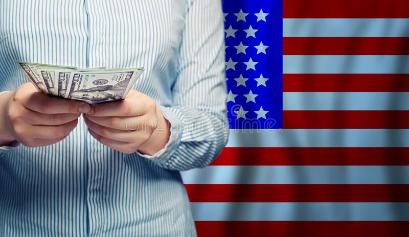 Hands counts money on American flag background.  stock images
