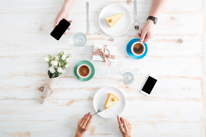 Hands of couple eating cakes and using smartphones on table stock photography