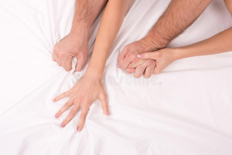 Hands of couple who making love in bed on white crumpled sheet, focus on hands stock photography
