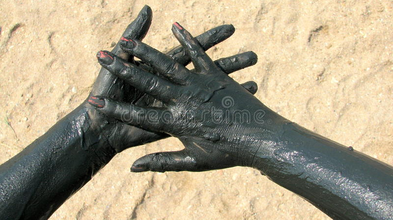 Hands covered with therapeutic mud. Picture taken at Techirghiol lake. Techirghiol is a lake in Northern Dobrogea, Romania, near the town with the same name. In royalty free stock images