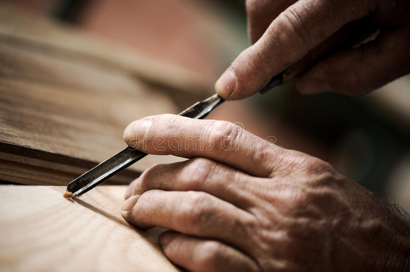 Hands of a craftsman. Hands of the craftsman carve a bas-relief with a gouge stock images