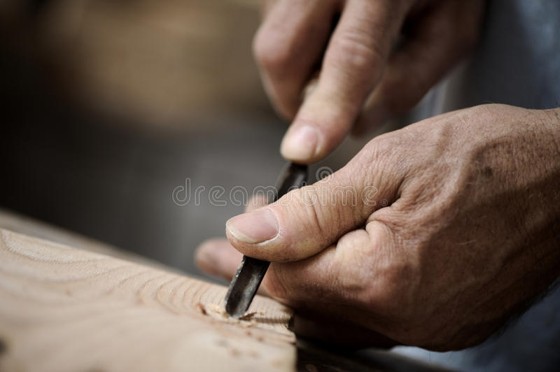 Hands of a craftsman. Hands of the craftsman carve a bas-relief with a gouge stock photo