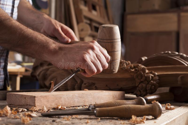 Hands of craftsman carve with a gouge. In the hands on the workbench in carpentry royalty free stock photo