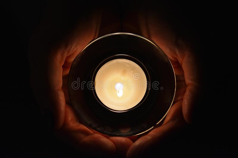 Burning tealight in cupping hands. Closeup on female hands holding a burning tealight. Top view royalty free stock image