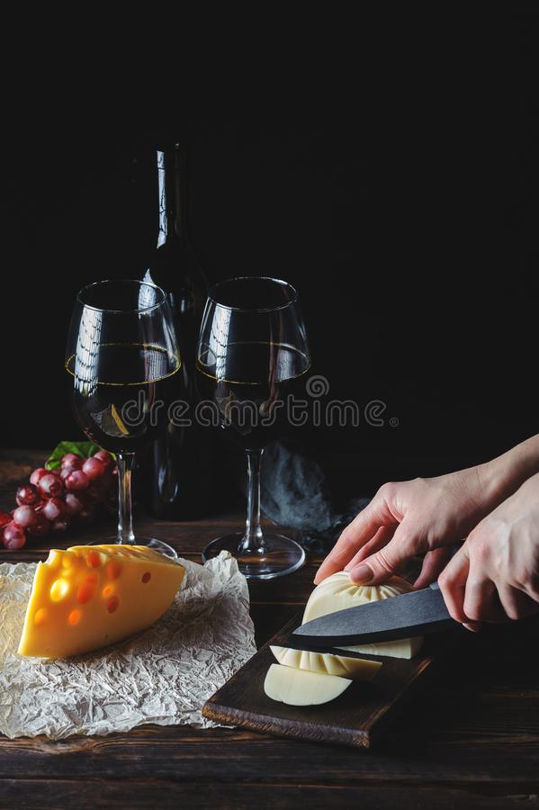 Hands cut the cheese to wine royalty free stock images