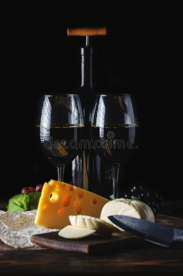 Hands cut the cheese to wine stock photo