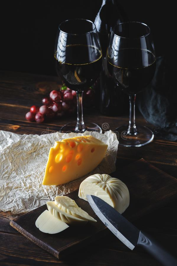 Hands cut the cheese to wine stock images