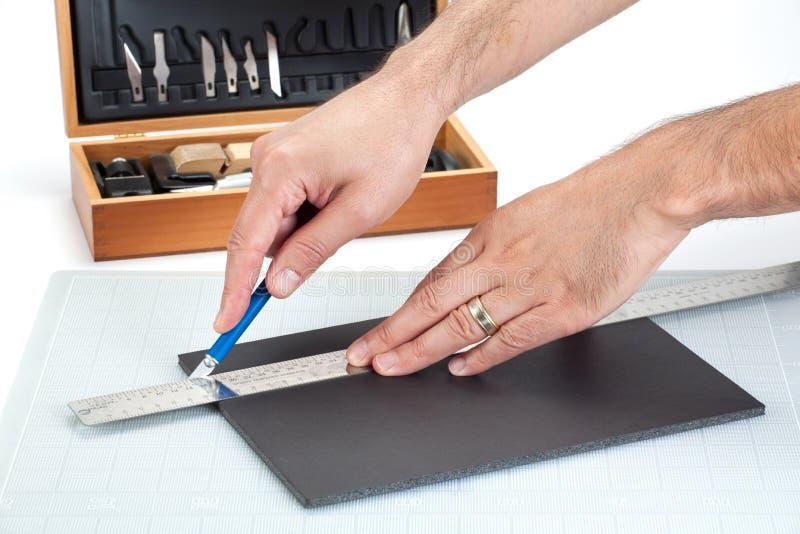 Hands cutting a foam board with sharp knife. Hands cutting on board with sharp knife stock photography