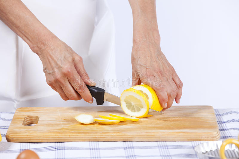 Hands cutting lemon stock photo