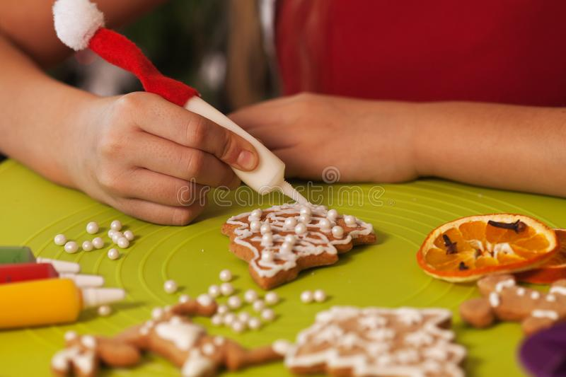 Hands decorating the christmas gingerbread cookies - closeup royalty free stock images