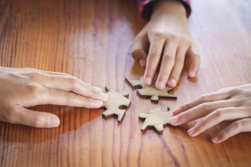 Hands of diverse people assembling jigsaw puzzle, team put pieces together searching for right match, help support in teamwork to stock photos