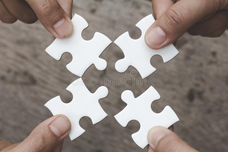 Hands of diverse people assembling jigsaw puzzle, Youth team put pieces together searching for right match, help support in royalty free stock images