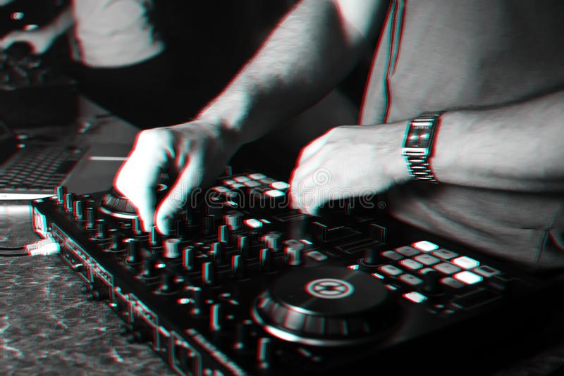 Hands of a DJ in a booth playing on the mixer. In the club. Black and white photo with glitch effect and small grain royalty free stock photography