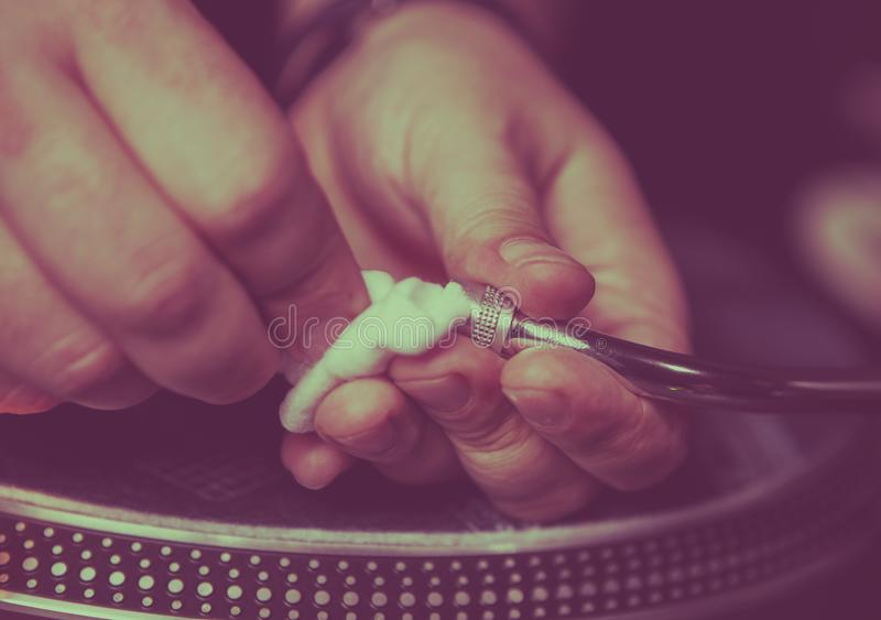 Dj cleans turntables needle in close up royalty free stock image