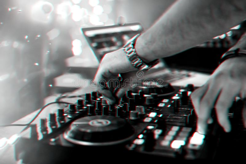 Hands DJ mixing and playing music on a professional controller mixer. Board in a nightclub at a party. Black and white photo with glitch effect and small grain royalty free stock image